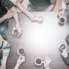 Creative Setting: Students sitting around table drinking coffee in college cafe
